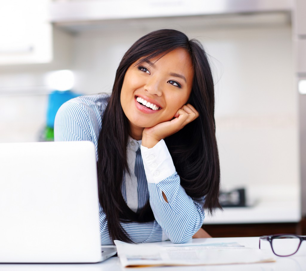 Happy beautiful dreamy businesswoman sitting in office